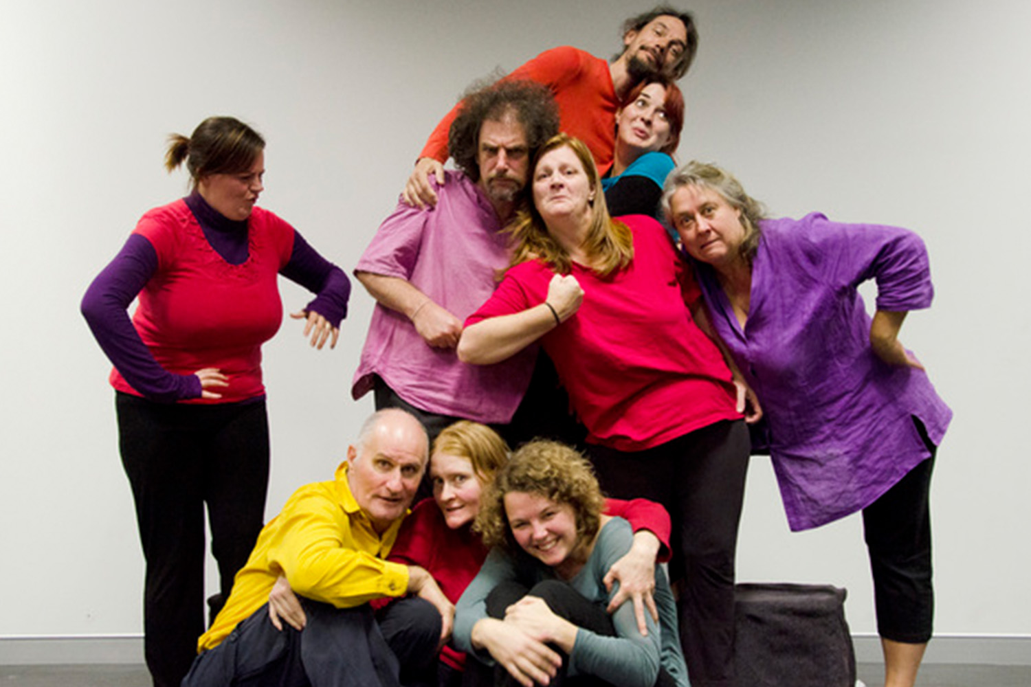 A group of actors pose in various positions
