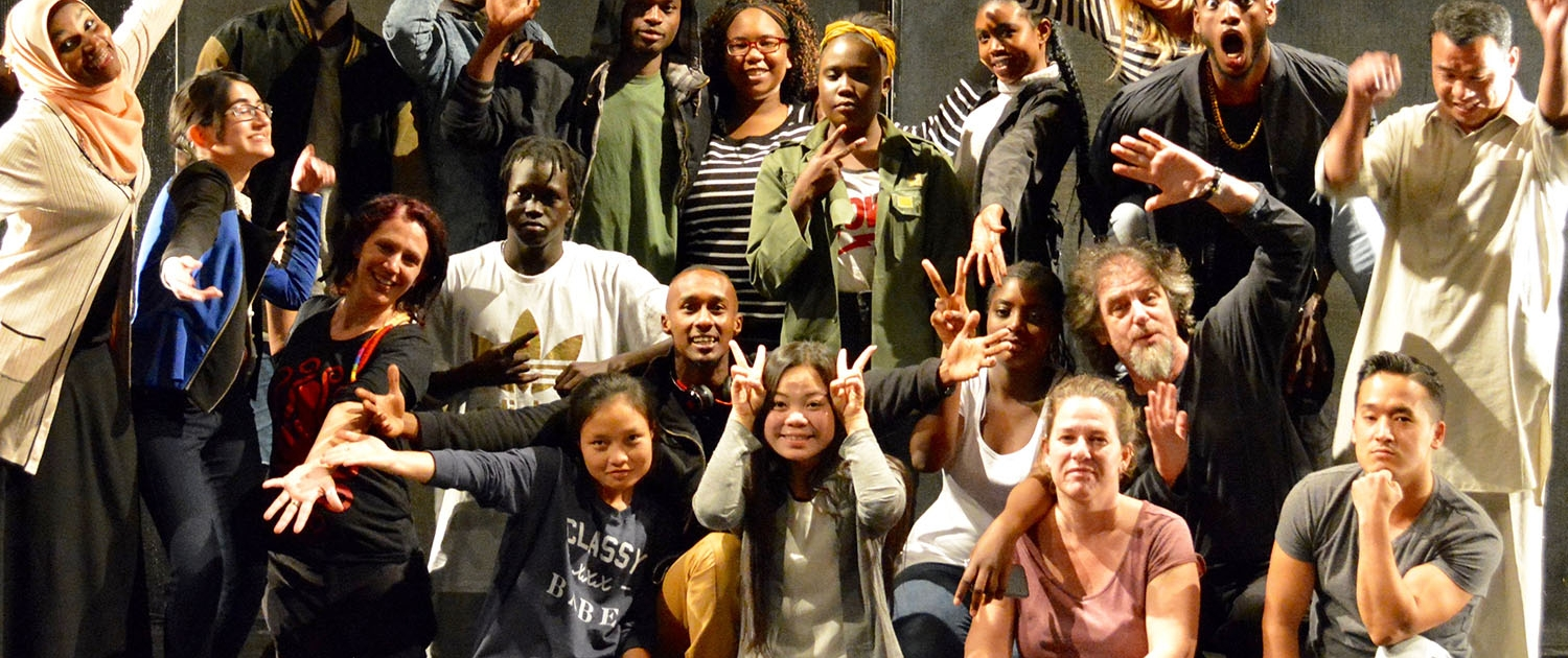 A multicultural group of actors smiles at the camera