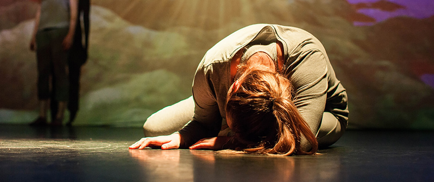 A woman lies on the floor in the foetal position